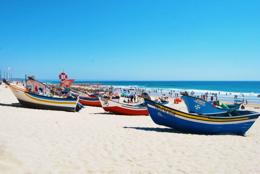 Boats on Costa da Caparica beach Portugal - one of the best beaches near Lisbon